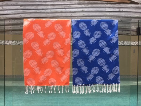 Tow pineapple design towels hanging over a glass pool fence