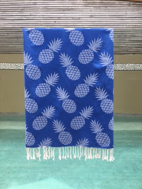 Pineapple design towel hanging over a glass pool fence