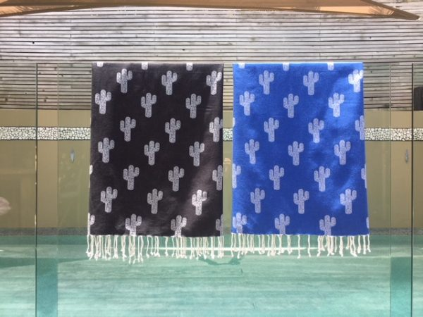 two towels hanging over a glass pool fence