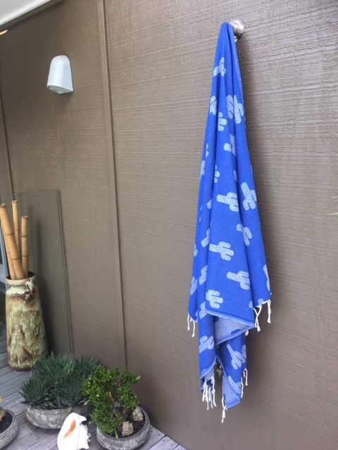 Blue towel with cactus design hanging by an outdoor shower