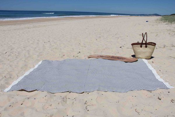 Beach towel at the beach with basket and surf board