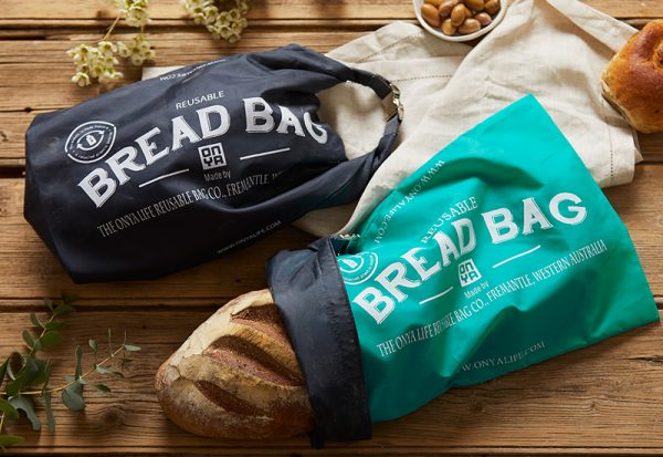 Loaves of bread in reusable bags on a bench