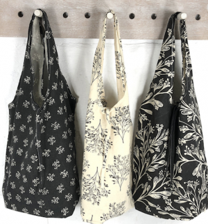 Three reusable bags on a coat rack
