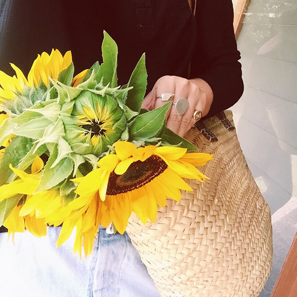Girl holding a hand woven basket full of sunflowers
