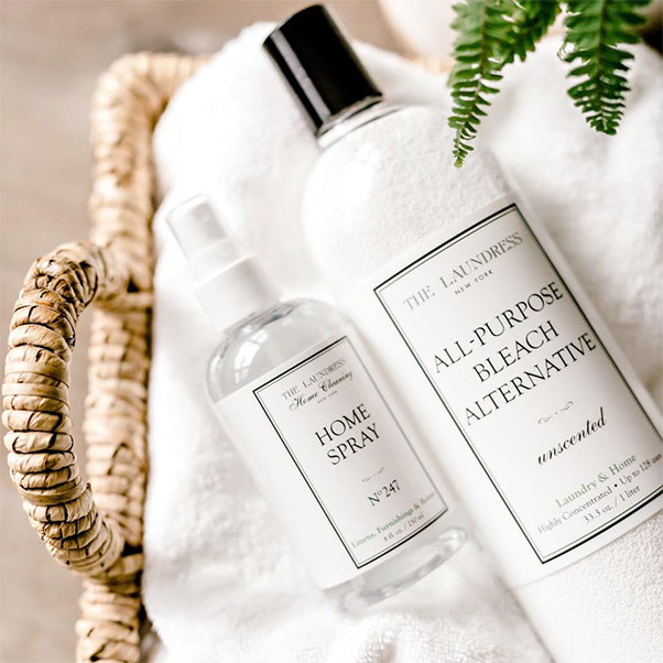The Laundress home spray and all purpose bleach alternative in a basket with towels